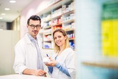 Two pharmacists working in a drugstore. Two friendly pharmacists working in a drugstore stock image