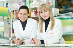 Two Pharmacy chemist women in drugstore Stock Image