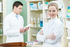 Two Pharmacy chemist workers in drugstore Stock Photos