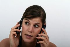 On Two Phones. A young woman speaking on two phones being stressed Stock Image