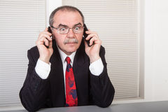 Two phones. Senior businessman working in office with two phones Stock Photo