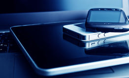 Two phones and tablet pc on laptop Stock Photos