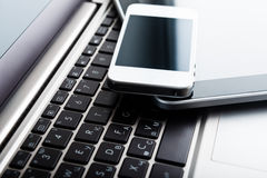 Two phones and tablet pc on laptop Royalty Free Stock Images