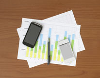 Two Phones & Two Charts on the Table Royalty Free Stock Photo