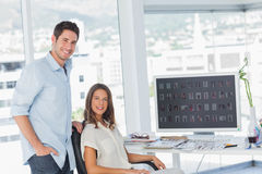 Two photo editors posing in their office. Next to a computer Stock Image