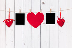 Two photo frame blank and red heart hanging on white wood backgr Stock Photos