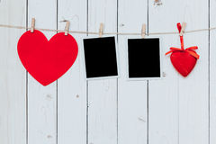 Two photo frame blank and red heart hanging on white wood backgr Royalty Free Stock Photography