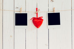 Two photo frame blank and red heart hanging on white wood with s Stock Photography