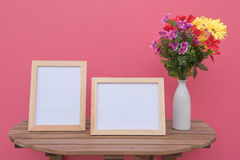 Two photo Frame on a wooden and Flowers in jar on pink background . Royalty Free Stock Photo