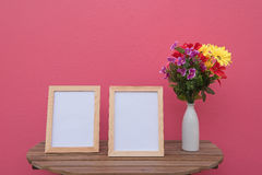 Two photo Frame on a wooden and Flowers in jar on pink background . Stock Photography