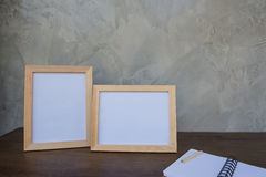 Two photo Frame on a wooden table and book on Gray wall background . Royalty Free Stock Photo