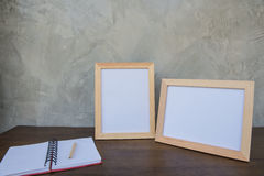 Two photo Frame on a wooden table and book on Gray wall background . Stock Photo