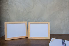 Two photo Frame on a wooden table and book on Gray wall background . Royalty Free Stock Photos