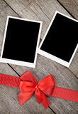 Two photo frames over wooden background with red bow Royalty Free Stock Photo