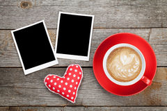 Two photo frames over wooden background with red coffee cup Royalty Free Stock Photos