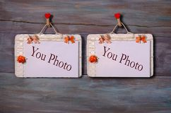 Two photo paper attach to rope with clothes pins on wooden background Royalty Free Stock Images