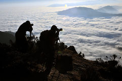 Two Photographer in mountains. Male photographer taking sea of clouds pictures in china Minya Konka Mountains in Tibetan Plateau Royalty Free Stock Photography
