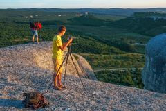 Two photographers takes pictures of nature on the rock. In the evening Royalty Free Stock Photography