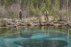 Two photographers taking pictures near a geyser lake Stock Images