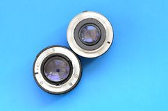 Two photographic lenses lie on a bright blue background. Space f stock images