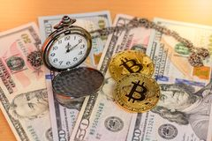 Two physical golden bitcoins with pocket watch on us dollars. With sun flare Stock Photos