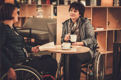 Two physically challenged women in a cafe.  Royalty Free Stock Images
