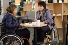 Two physically challenged women in a cafe.  Stock Photos