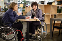 Two physically challenged women in a cafe.  Royalty Free Stock Image