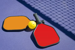 Two Pickleball Paddles and a pickleball on court with net shadow