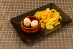 Two pickled eggs with crisps or chips. Two pickled eggs in ceramic bowl, served with crisps or chips Stock Photography