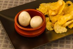 Two pickled eggs with crisps or chips. Two pickled eggs in ceramic bowl, served with crisps or chips Stock Photo