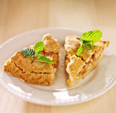 Two pieces of apple pie with mint garnish. Stock Photo