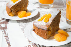 Two pieces of apricot pie on the white plates. Two pieces of apricot pie, decorated by dried apricots on the white plate. Orange juice in the background.The royalty free stock photos