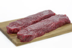 Two pieces of beef on a wooden board Stock Photos