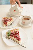 Two pieces of berry pie with whipped cream filling and a cup of tea. On white table Stock Photo