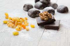 Two pieces of black chocolate and a wallnut on it. Royalty Free Stock Photos