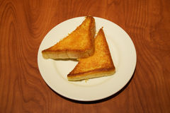 Two pieces of buttered toast in white plate on wooden table Stock Photo