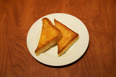 Two pieces of buttered toast in white plate on wooden table Stock Photography
