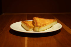 Two pieces of buttered toast in white plate on wooden table Stock Photos