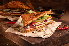 Two pieces of club sandwich on old papper with big cutting board Stock Image