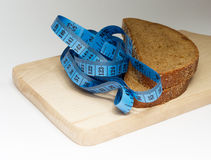 Two pieces of dark bread and blue meter on the board Royalty Free Stock Photography