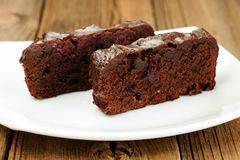 Two pieces of dark chocolate cake with cherries in white plate Royalty Free Stock Images