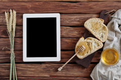 Two pieces of fresh bread with homemade honey on a wooden table. Closeup. Next tablet with blank screen. Top view. Free space for text. Copy space Stock Photo