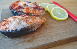 Two pieces of fresh fish with lemon and soy sauce. Two pieces of fresh red fish with lemon and soy sauce Stock Photos