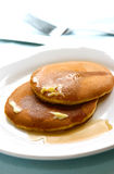 Two pieces of freshly cooked pancake drizzled with maple syrup Royalty Free Stock Photos