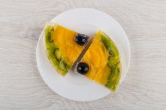 Two pieces of fruit pie in white plate on table. Two pieces of fruit pie in white plate on wooden table. Top view stock photos