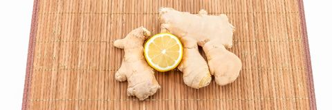 Two pieces of ginger and half a fresh lemon on a bamboo mat. View from above. stock images