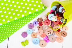 Two pieces of green fabric with polka dot pattern, colorful buttons set. Sewing background Stock Image