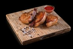 Two pieces of of grilled pork on a black background, horizontal close-up. stock photography