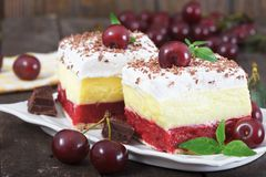 Two pieces of homemade cherry cake with vanilla and whipping cream. Cherries on top of the cakes. Rustic style, wooden background Royalty Free Stock Image